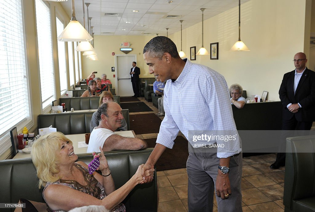 US President Barack Obama greets dinners after ordering pie from a local restaurant in Lenox, Pennsylvania, on August 23, 2013. Obama is on a two-day bus tour through New York and Pennsylvania to discuss his plan to make college more affordable, tackle rising costs, and improve value for students and their families. AFP Photo/Jewel Samad