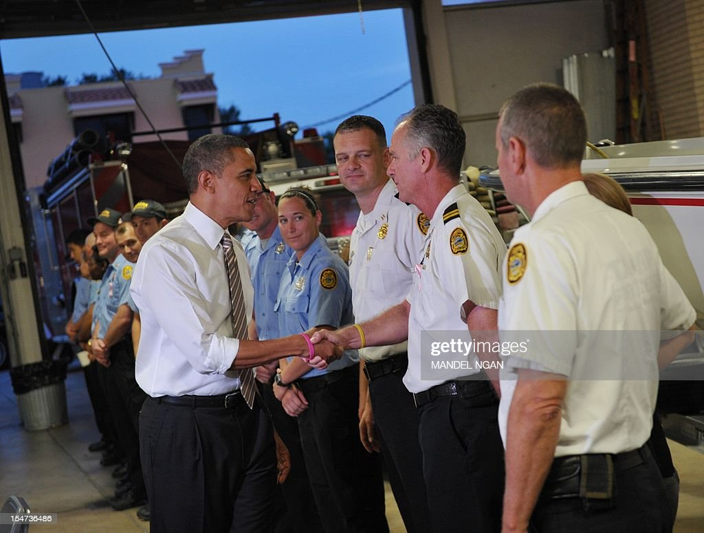 US President Barack Obama greets firefighters after dropping off doughnuts for them at a fire station in Tampa, Florida, on October 25, 2012. Obama pursued the sunset west then turned around and chased the dawn, streaking across America on an eight-state marathon as his re-election bid hit top gear. AFP PHOTO / Mandel NGAN