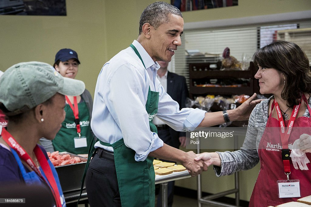 U.S. President Barack Obama greets furloughed federal worker U.S. Census Burea employee Dolly Garcia (R) during a visit to a Martha's Table kitchen on October 14, 2013 in Washington, D.C. During a statement, Obama called on congress to end the budget stalemate and allow federal employees to return to work.