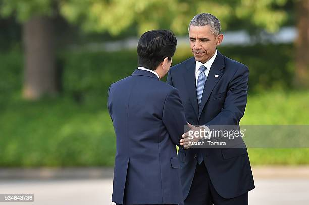 S President Barack Obama greets Japanese Prime Minister Shinzo Abe during his visit to the Hiroshima Peace Memorial Park on May 27 2016 in Hiroshima...