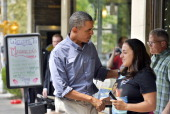 US President Barack Obama greets locals outside a restaurant in Rochester New York on August 22 2013 Obama is on a twoday bus tour through New York...