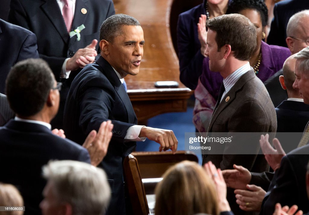 U.S. President <a gi-track='captionPersonalityLinkClicked' href=/galleries/search?phrase=Barack+Obama&family=editorial&specificpeople=203260 ng-click='$event.stopPropagation()'>Barack Obama</a> greets members of Congress as he arrives to deliver the State of the Union address to a joint session of Congress at the Capitol in Washington, D.C., U.S., on Tuesday, Feb. 12, 2013. Obama called for raising the federal minimum wage to $9 an hour and warned he'll use executive powers to get his way on issues from climate change to manufacturing if Congress doesn't act, laying out an assertive second-term agenda sure to provoke Republicans. Photographer: Joshua Roberts/Bloomberg via Getty Images
