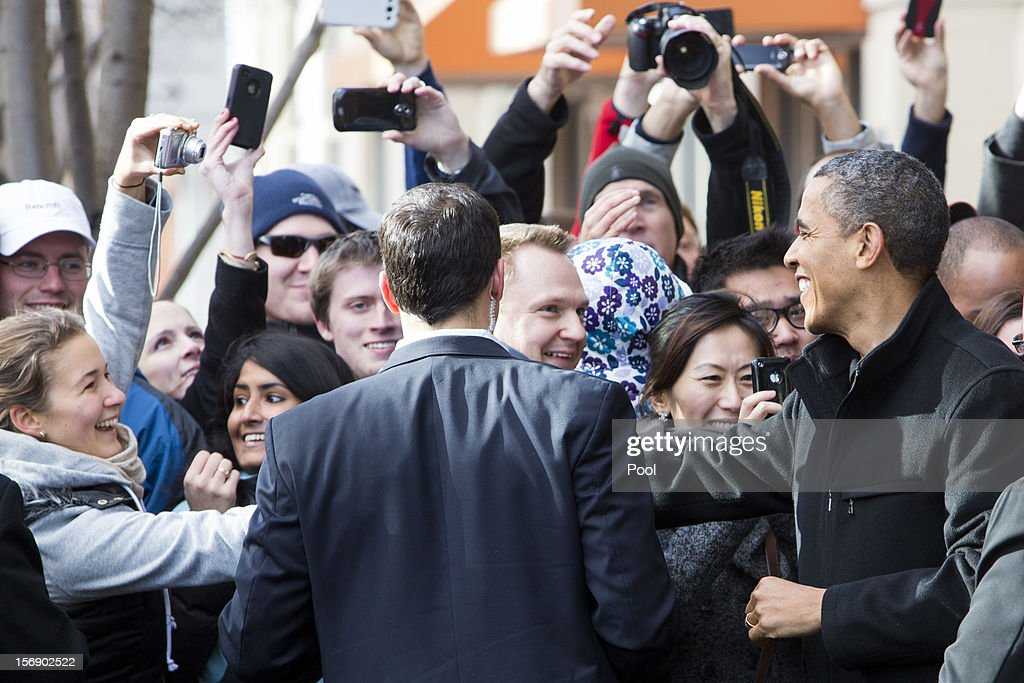 U.S. President <a gi-track='captionPersonalityLinkClicked' href=/galleries/search?phrase=Barack+Obama&family=editorial&specificpeople=203260 ng-click='$event.stopPropagation()'>Barack Obama</a> (R) greets onlookers after shopping with his daughters at One More Page Books on Small Business Saturday November 24, 2012 in Arlington, Virginia. Obama urged Americans to participate in Small Business Saturday as an alternative to Black Friday and Cyber Monday.