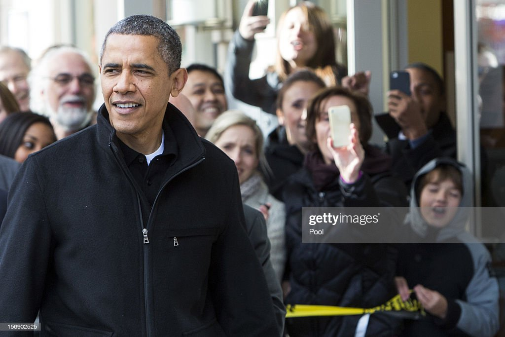 U.S. President <a gi-track='captionPersonalityLinkClicked' href=/galleries/search?phrase=Barack+Obama&family=editorial&specificpeople=203260 ng-click='$event.stopPropagation()'>Barack Obama</a> greets onlookers after shopping with his daughters at One More Page Books on Small Business Saturday November 24, 2012 in Arlington, Virginia. Obama urged Americans to participate in Small Business Saturday as an alternative to Black Friday and Cyber Monday.