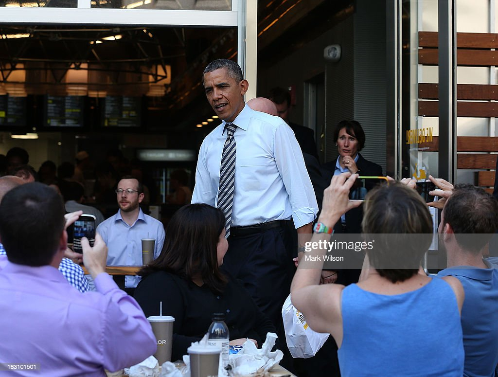 President Barack Obama greets people as he walks out of the Taylor Gourmet Deli, October 4, 2013 in Washington, DC. Democrats and Republicans are still at a stalemate on funding for the federal government as the shut down goes into the fourth day.