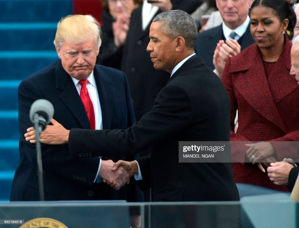 President Barack Obama (R) greets President-elect Donald Trump as he arrives on the platform at the US Capitol in Washington, DC, on January 20, 2017, before his swearing-in ceremony. / AFP PHOTO / Mandel NGAN