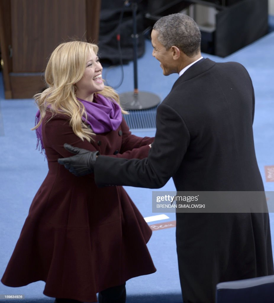 US President Barack Obama greets singer Kelly Clarkson (C) after Obama took the oath of office during the 57th Presidential Inauguration ceremonial swearing-in at the US Capitol on January 21, 2013 in Washington, DC. The oath was administered by US Supreme Court Chief Justice John Roberts. AFP PHOTO/Brendan SMIALOWSKI