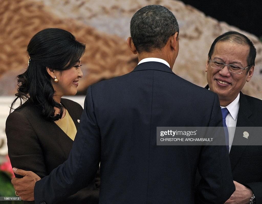 US President Barack Obama (C) greets Thai Prime Minister Yingluck Shinawatra (L) and Philippines President Benigno Aquino ahead of a family picture preceding the 7th East Asia Summit in Phnom Penh on November 20, 2012. Obama was set to defy Beijing's protests and use a summit to raise concerns over South China Sea rows that have sent diplomatic and trade shockwaves across the region. AFP PHOTO/Christophe ARCHAMBAULT