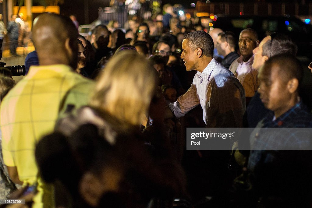US President <a gi-track='captionPersonalityLinkClicked' href=/galleries/search?phrase=Barack+Obama&family=editorial&specificpeople=203260 ng-click='$event.stopPropagation()'>Barack Obama</a> greets well wishers before boarding Air Force One at Joint Base Pearl Harbor-Hickam on December 26, 2012 in Honolulu, Hawaii. The president, who was spending a traditional Christmas holiday with his family in Hawaii, has been forced to cut his Christmas break short by the fiscal cliff crisis.