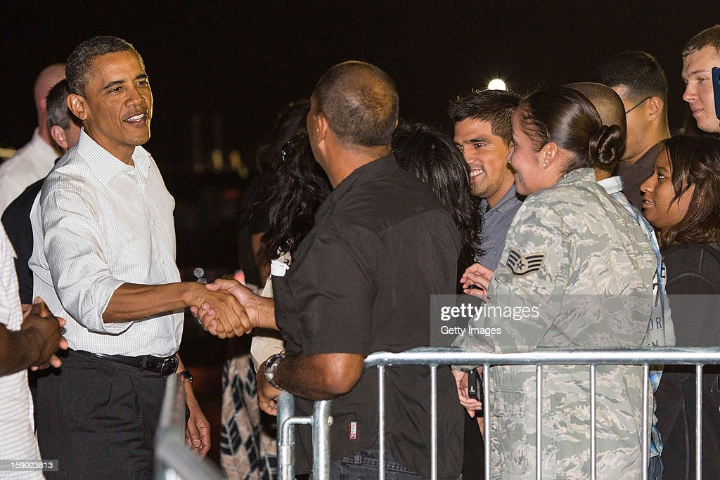 US President <a gi-track='captionPersonalityLinkClicked' href=/galleries/search?phrase=Barack+Obama&family=editorial&specificpeople=203260 ng-click='$event.stopPropagation()'>Barack Obama</a> greets well wishers before boarding Air Force One at Joint Base Pearl Harbor-Hickam on January 5, 2013 in Honolulu, Hawaii. The president had to cut short his vacation to work in Washington on efforts to avert the recent fiscal cliff crisis and then returned to Hawaii to be with his family.