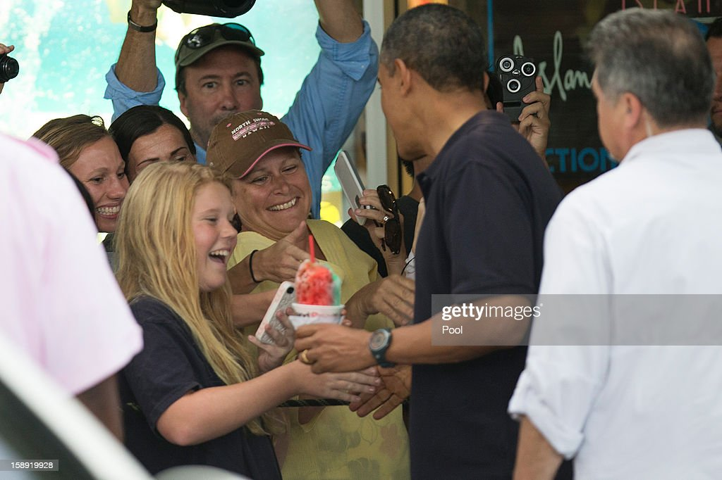 U.S. President Barack Obama greets well wishers outside of Island Snow on January 3, 2013 in Kailua, Hawaii. The president, having cut short his holiday vacation to work in Washington on efforts to avert the recent fiscal cliff crisis, returned to Hawaii on Wednesday to be with the first lady and and his daughters.