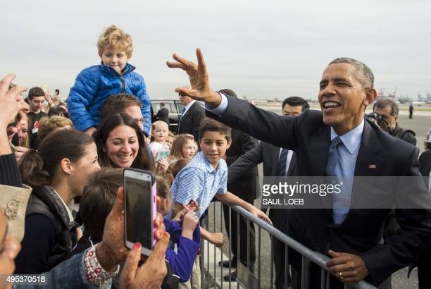 US President Barack Obama greets well wishers upon arrival at Newark Liberty International Airport in Newark New Jersey November 2 2015 Obama is...