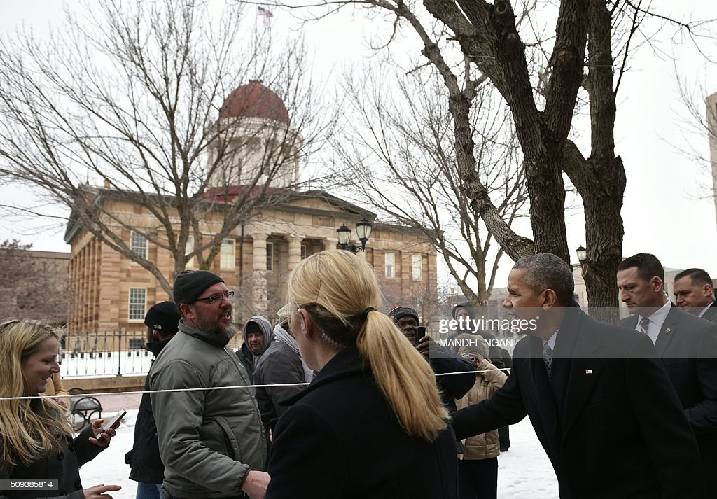 US President Barack Obama greets well-wishers after stopping by a restaurant to pick up lunch in front of the Old State Capitol in Springfield, Illinois on February 10, 2016. / AFP / Mandel Ngan