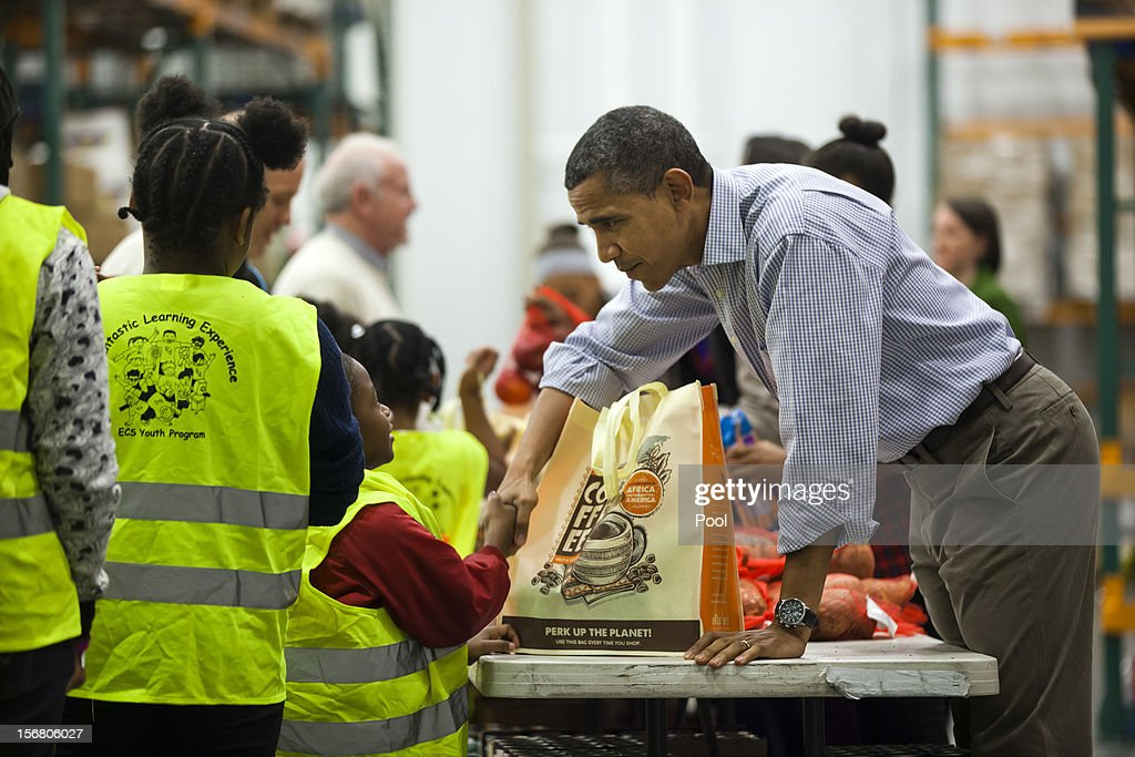U.S. President Barack Obama hands out food to the needy for Thanksgiving at the Capitol Area Food Bank on November 21, 2012 in Washington, DC. President Obama also marked the Thanksgiving holiday today with the traditional Thanksgiving turkey pardon at the White House.