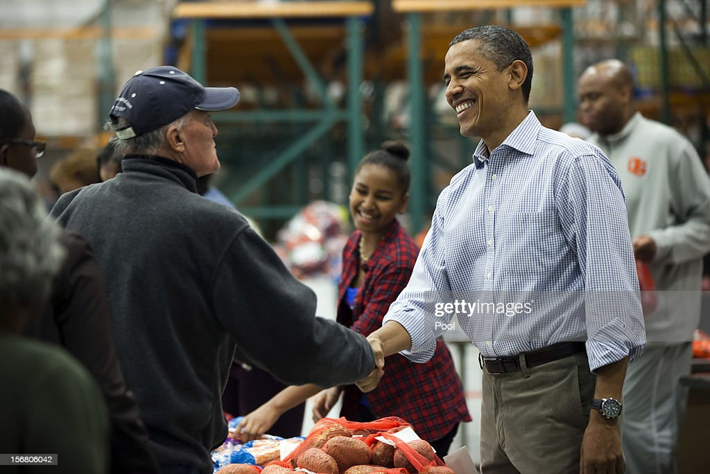 U.S. President Barack Obama hands out food to the needy for Thanksgiving at the Capitol Area Food Bank on November 21, 2012 in Washington, DC. Obama also celebrated the traditional Thanksgiving turkey pardon at the White House.