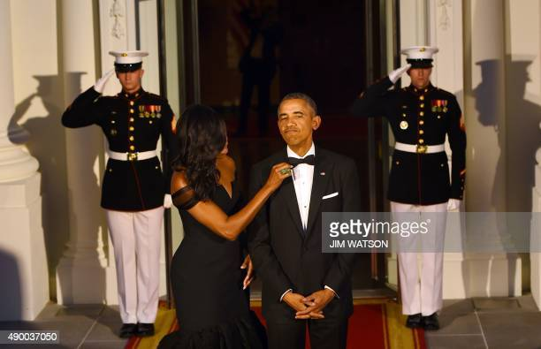 US President Barack Obama has his tie adjusted by US First Lady Michelle Obama as they await the arrival of Chinese President Xi Jinping and his wife...