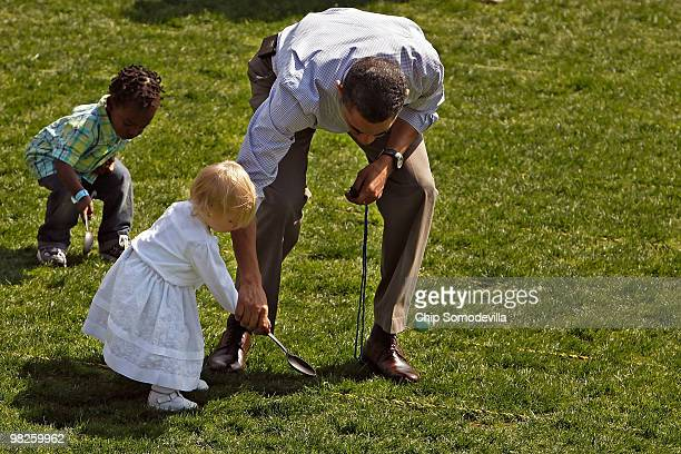S President Barack Obama helps a girl move her egg down the lawn during the Easter Egg Roll at the White House April 5 2010 in Washington DC About...