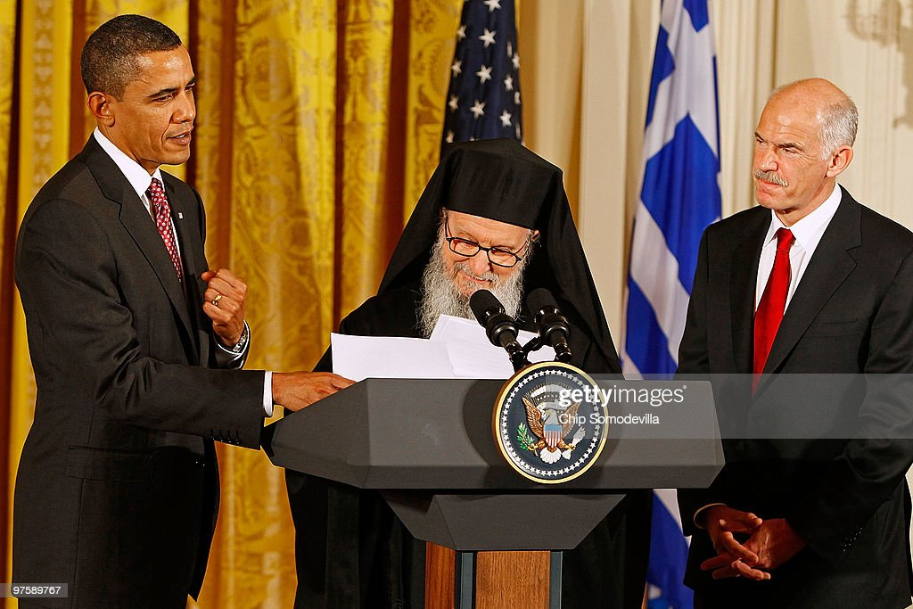 U.S. President <a gi-track='captionPersonalityLinkClicked' href=/galleries/search?phrase=Barack+Obama&family=editorial&specificpeople=203260 ng-click='$event.stopPropagation()'>Barack Obama</a> (L) helps Archbishop Demetrios, Primate of the Greek Orthodox Church in America, with his notes as Greek Prime Minister <a gi-track='captionPersonalityLinkClicked' href=/galleries/search?phrase=George+Papandreou&family=editorial&specificpeople=212855 ng-click='$event.stopPropagation()'>George Papandreou</a> looks on in the East Room of the White House March 9, 2010 in Washington, DC. Obama hosted the Greek Independence Day celebration two weeks ahead of the actual date, March 25, due to his upcoming trip to Asia.