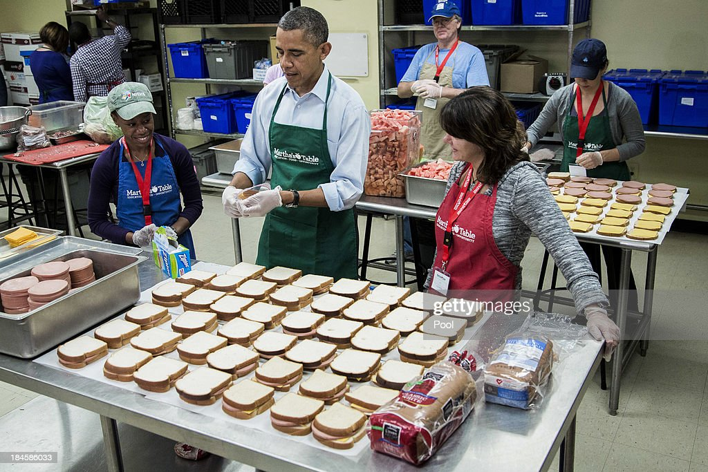 U.S. President Barack Obama (C) helps bag sandwiches with furloughed federal workers Health and Human Services employee Chantelle Burton (L) and U.S. Census Burea employee Dolly Garcia, while they volunteer at a Martha's Table kitchen on October 14, 2013 in Washington, D.C. During a statement, Obama called on congress to end the budget stalemate and allow federal employees to return to work.