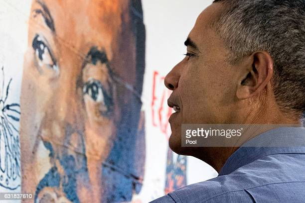 US President Barack Obama helps paint a mural depicting Martin Luther King Jr at the Jobs Have Priority Naylor Road Family Shelter January 16 2017 in...