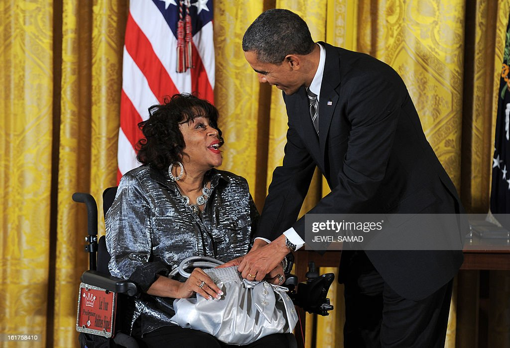 US President Barack Obama helps Women Embracing Abilities Now founder Janice Yvette Jackson to keep her 2012 Citizens Medal in her hand bag on February 15, 2013, during a ceremony in the East Room of the White House in Washington, DC. AFP PHOTO/Jewel Samad