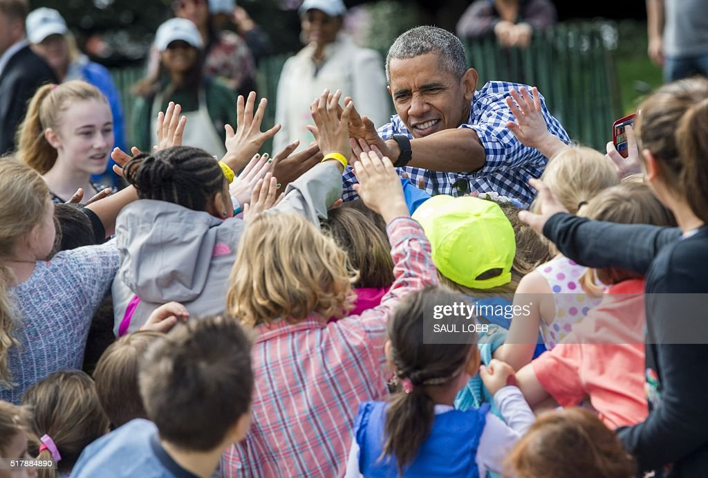 US President Barack Obama high fives children during the annual Easter Egg Roll on the South Lawn of the White House in Washington DC March 28 2016...