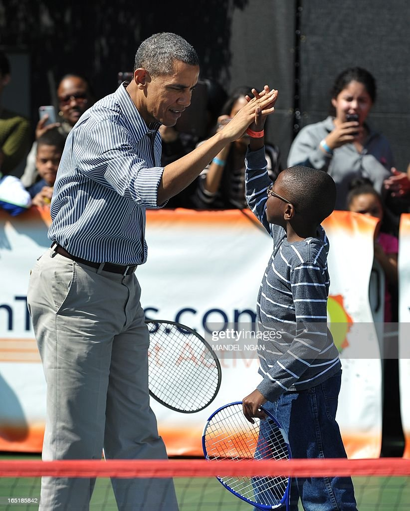 US President Barack Obama high-fives his doubles partner while playing tennis with children during the annual Easter Egg Roll on April 1, 2013 on the South Lawn of the White House in Washington, DC. AFP PHOTO/Mandel NGAN