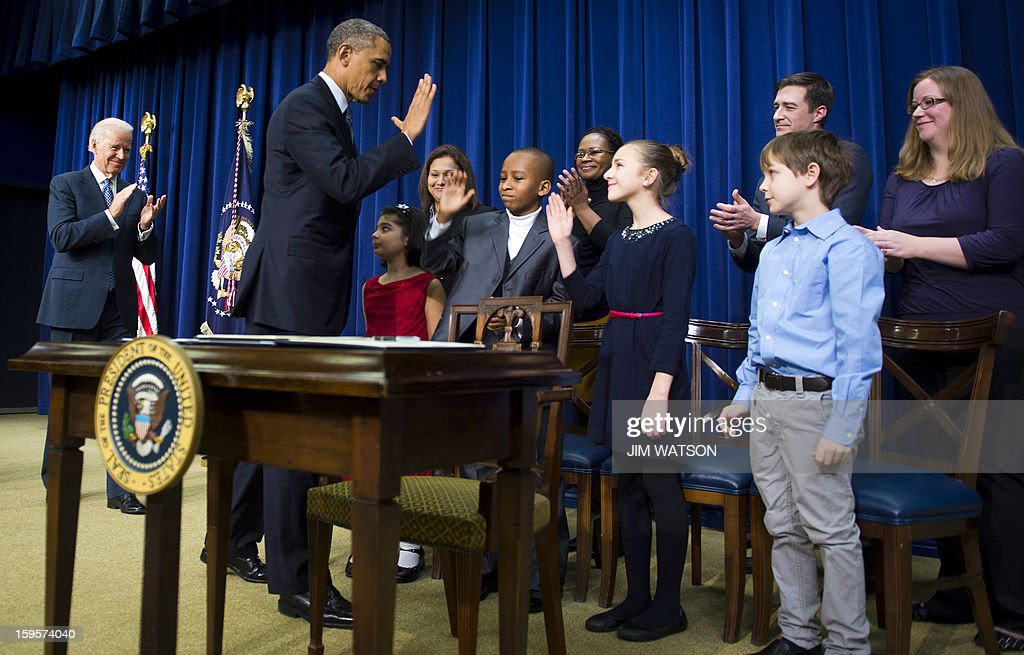 US President Barack Obama (2nd L) high-fives with children who wrote letters to his administration before signing executive orders during an event unveiling a package of proposals to reduce gun violence at the White House in Washington, DC, January 16, 2013. Obama signed 23 executive orders to curb gun violence and demanded Congress pass as assault weapons ban, in a sweeping set of measures in response to the Newtown massacre. AFP Photo/Jim WATSON