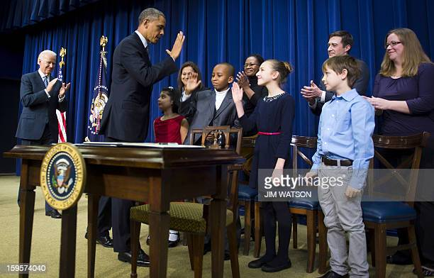 US President Barack Obama highfives with children who wrote letters to his administration before signing executive orders during an event unveiling a...