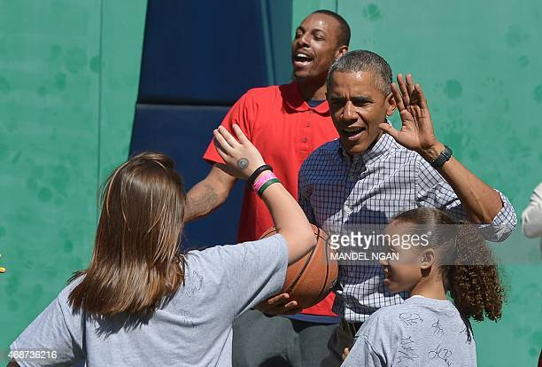 US President Barack Obama 'highfives'a child while playing basketball during the annual Easter Egg Roll on the South Lawn of the White House on April...
