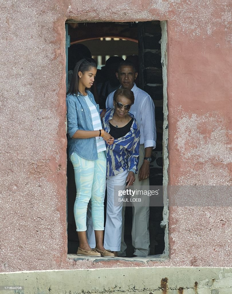 US President <a gi-track='captionPersonalityLinkClicked' href=/galleries/search?phrase=Barack+Obama&family=editorial&specificpeople=203260 ng-click='$event.stopPropagation()'>Barack Obama</a> (R), his daughter Malia Obama (L) and his mother-in-law, Marian Robinson look out from the Door of No Return during a visit to the House of Slaves, or Maison des Esclaves, at Goree Island off the coast of Dakar on June 27, 2013. Obama and his family toured the museum at the site where African slaves were held before going through the door and being shipped off the continent as slaves.