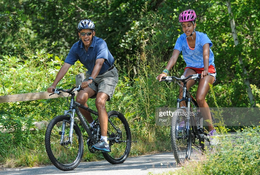 U.S. President <a gi-track='captionPersonalityLinkClicked' href=/galleries/search?phrase=Barack+Obama&family=editorial&specificpeople=203260 ng-click='$event.stopPropagation()'>Barack Obama</a> (L) his daughter <a gi-track='captionPersonalityLinkClicked' href=/galleries/search?phrase=Malia+Obama&family=editorial&specificpeople=2631620 ng-click='$event.stopPropagation()'>Malia Obama</a> ride a bike during a vacation on Martha's Vineyard August 16, 2013in West Tisbury, Massachusetts. Obama and his family are on a weeklong vacation.