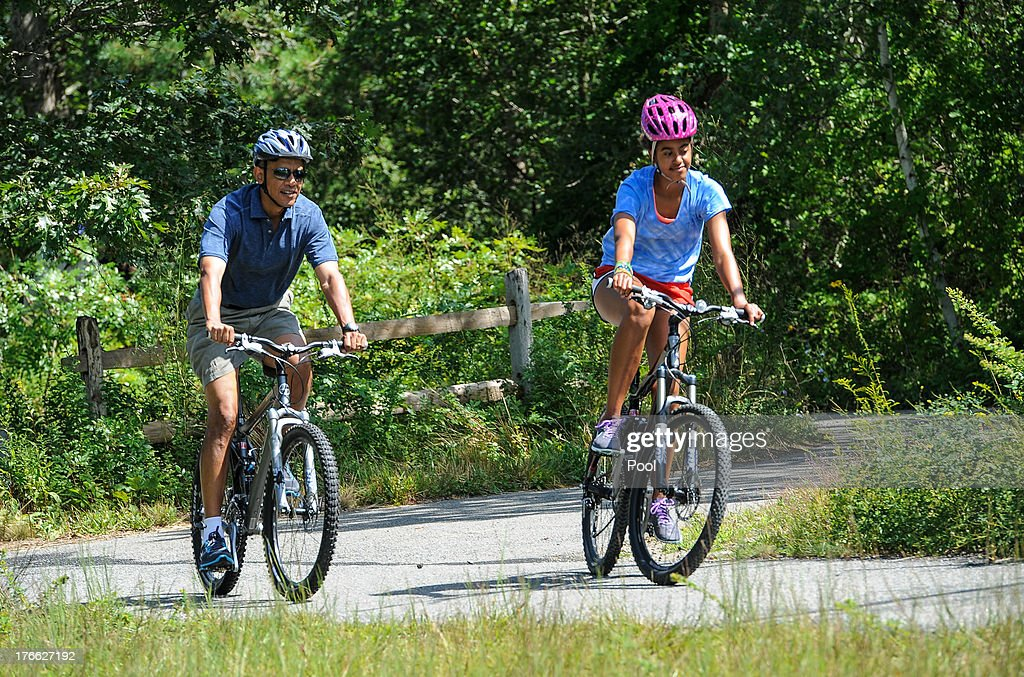U.S. President Barack Obama (L) his daughter Malia Obama ride a bike during a vacation on Martha's Vineyard August 16, 2013in West Tisbury, Massachusetts. Obama and his family are on a weeklong vacation.