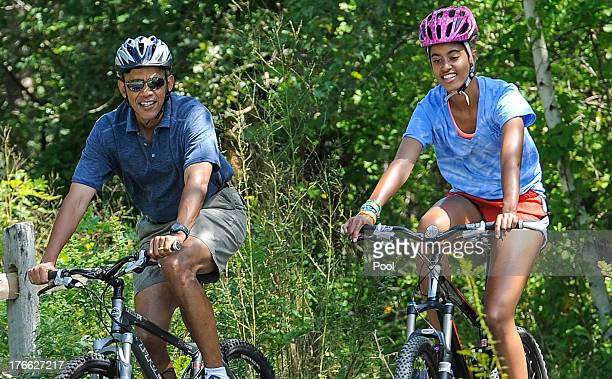 S President Barack Obama his daughter Malia Obama ride a bike during a vacation on Martha's Vineyard August 16 2013in West Tisbury Massachusetts...