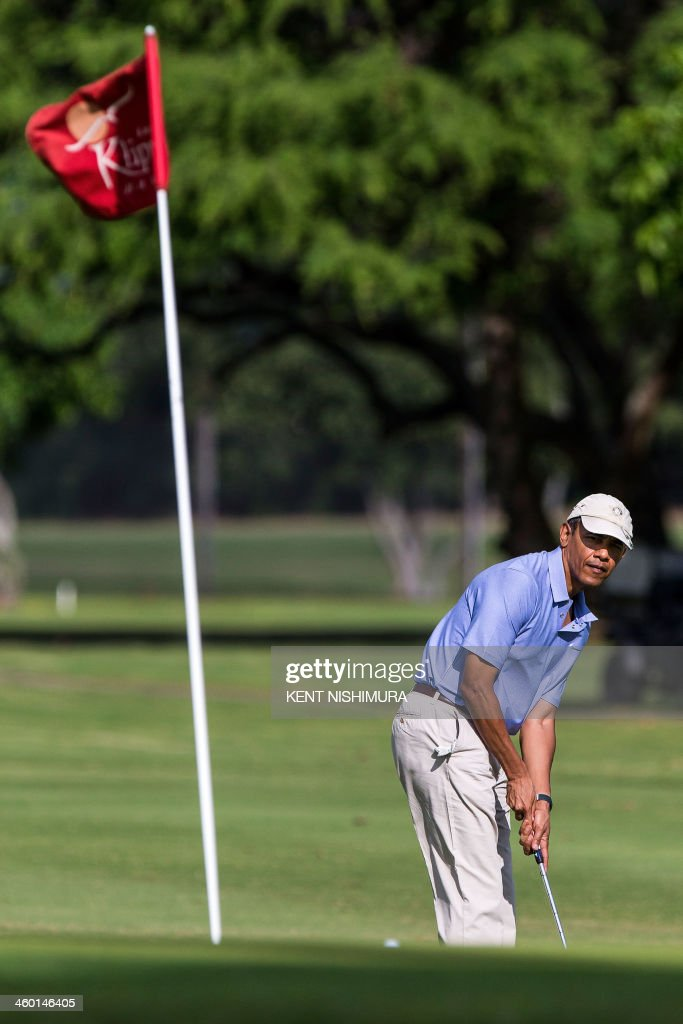 US President Barack Obama hits the ball on the second hole green at the Kaneohe Klipper Golf Course at Marine Corps Base Hawaii on January 2 2014 in...