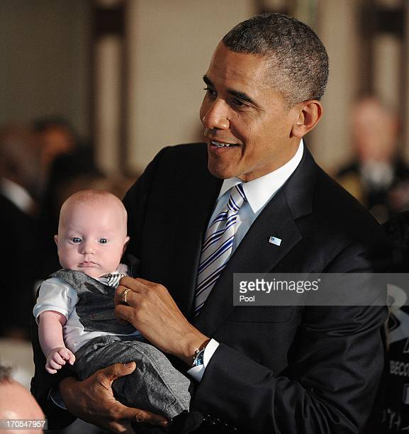 S President Barack Obama holds a baby at a Father's Day luncheon to celebrate the importance of strong families and mentorship in the State Dining...