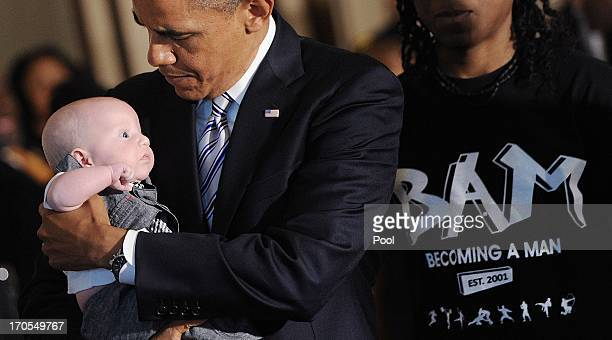 President Barack Obama holds a baby at a Father's Day luncheon to celebrate the importance of strong families and mentorship in the State Dining Room...