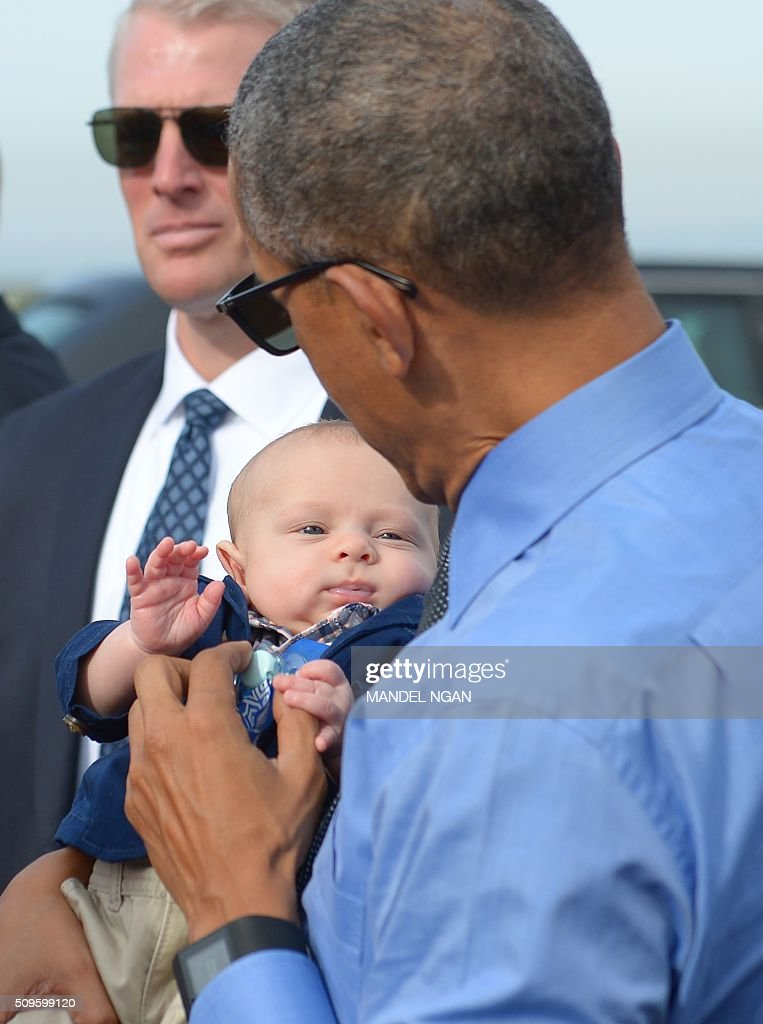 US President Barack Obama holds a baby while chating with well-wishers before boarding Air Force One upon departure from Moffett Federal Airfield in Mountain View, California on February 11, 2016. / AFP / MANDEL NGAN