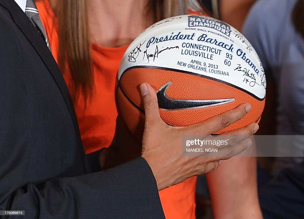 US President Barack Obama holds a basketball presented to him by the team during an event in honour of the 2013 NCAA Womens Basketball Champions, the University of Connecticut Huskies, in the East Room of the White House on July 31, 2013 in Washington, DC. AFP PHOTO/Mandel NGAN