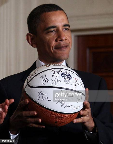 S President Barack Obama holds a basketball presented to him by the NCAA champions University of Connecticut women�s basketball team during a...