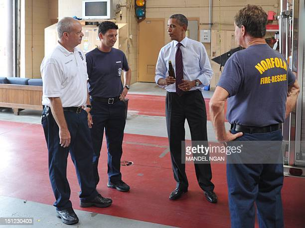 US President Barack Obama holds a bottle of ale as he presents a case of White House brew to firefighters during an unannounced stop at Fire Station...