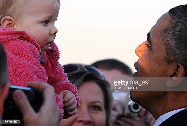 US President Barack Obama holds a child as he greets people at the O'Hare International Airport in Chicago Illinois on January 11 2012 upon arrival...