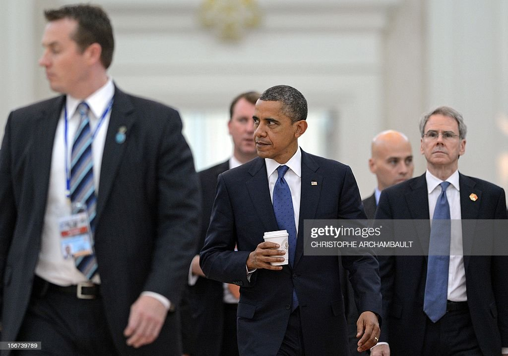 US President Barack Obama (C) holds a glass as he leaves the venue during a break at the 7th East Asia Summit in Phnom-Penh on November 20, 2012. Obama was set to defy Beijing's protests and use a summit to raise concerns over South China Sea rows that have sent diplomatic and trade shockwaves across the region. AFP PHOTO/Christophe ARCHAMBAULT