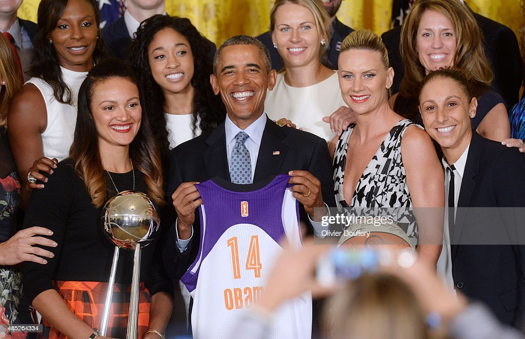 President Barack Obama holds a jersey given to him by the WNBA champion Phoenix Mercury during an event in the East Room at the White House on August...