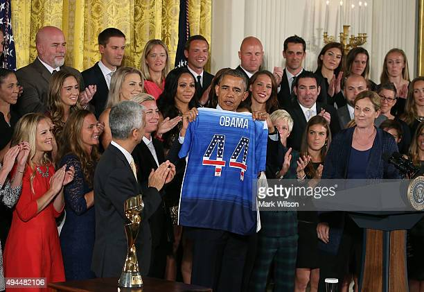 President Barack Obama holds a jersey given to him by the World Champion United States Women's National Soccer Team in the East Room of the White...
