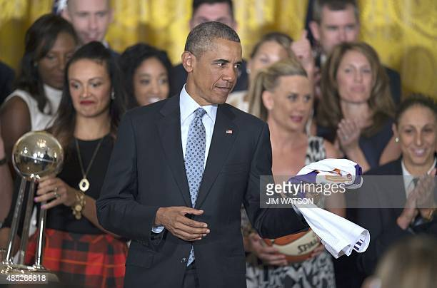 US President Barack Obama holds a jersey given to him during an event congratulating the 2014 WNBA champions Phoenix Mercury at the White House in...