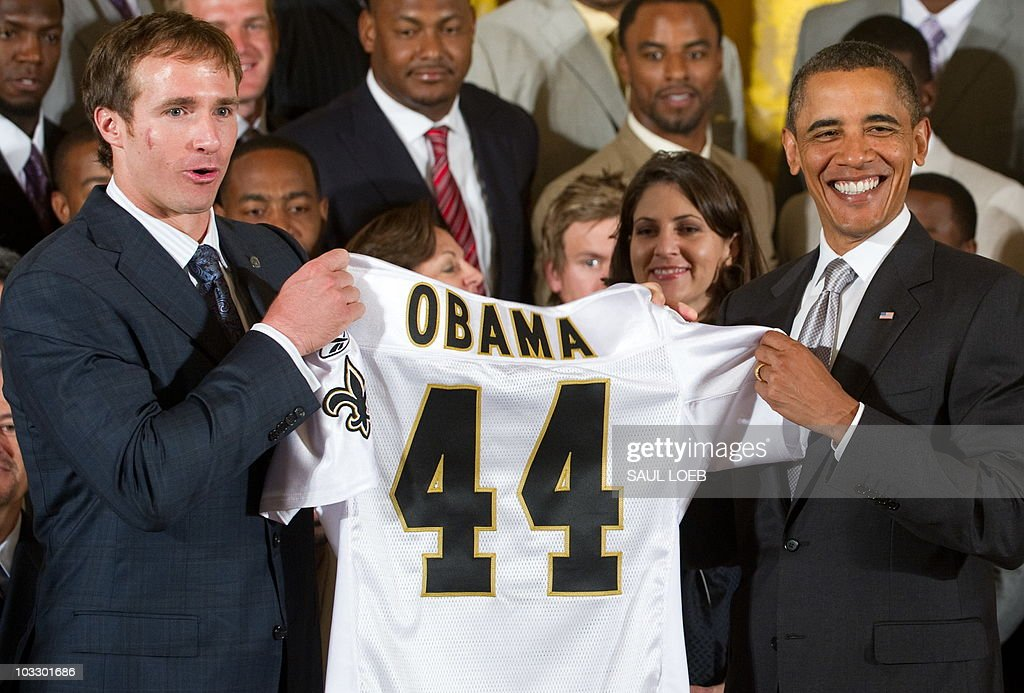US President Barack Obama holds a jersey presented to him by 2010 Super Bowl MVP Drew Brees (L) during an event honoring the 2010 Super Bowl Champion New Orleans Saints in the East Room at the White House in Washington, DC, August 9, 2010. AFP PHOTO / Saul LOEB