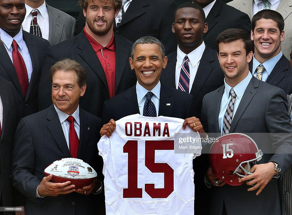 President <a gi-track='captionPersonalityLinkClicked' href=/galleries/search?phrase=Barack+Obama&family=editorial&specificpeople=203260 ng-click='$event.stopPropagation()'>Barack Obama</a> (C), holds a #15 jersey presented to him by coach <a gi-track='captionPersonalityLinkClicked' href=/galleries/search?phrase=Nick+Saban&family=editorial&specificpeople=242860 ng-click='$event.stopPropagation()'>Nick Saban</a> (L) and Quaterback <a gi-track='captionPersonalityLinkClicked' href=/galleries/search?phrase=A.J.+McCarron&family=editorial&specificpeople=6548267 ng-click='$event.stopPropagation()'>A.J. McCarron</a> (R), while honoring the BCS National Champion University of Alabama Crimson Tide, during an event at the White House, April 15, 2013 in Washington, DC. The Crimson tide finished the season with a record of 13 wins and one loss and defeated Notre dame in the BCS championship game.