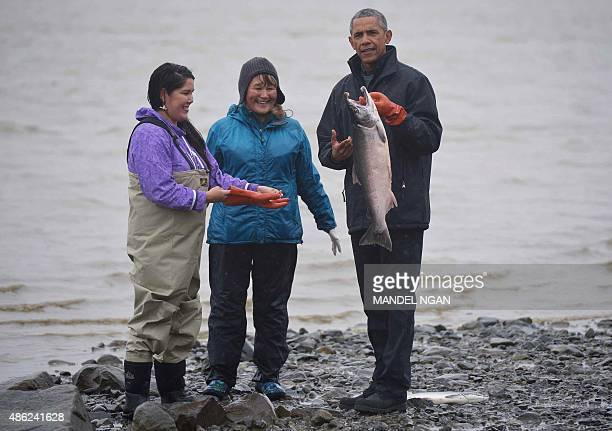 US President Barack Obama holds a silver salmon while meeting with local fishermen and their families on Kanakanak Beach in Dillingham Alaska on...