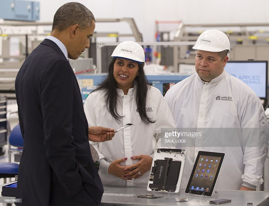 US President Barack Obama holds a smartphone component while speaking with employees at Applied Materials, a manufacturer of systems for polishing the surface of unfinished semiconductor chips, in Austin, Texas, May 9, 2013. AFP PHOTO / Saul LOEB